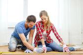 Smiling couple measuring wood flooring — Stock Photo