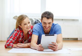 Smiling couple looking at tablet pc at home — Stock Photo