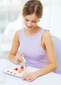 Smiling young woman eating dessert at restaurant — Photo