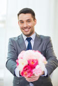 Smiling handsome man giving bouquet of flowers — Photo
