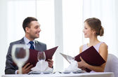 Smiling couple with menus at restaurant — Photo