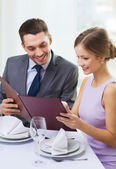 Smiling couple with menu at restaurant — Photo