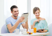 Smiling couple with tablet pc reading news — Stock Photo