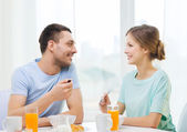 Smiling couple having breakfast at home — Stock Photo
