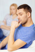Upset young man with man on the back at home — Stock Photo