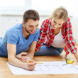 Smiling couple looking at blueprint at home — Stock Photo #43220461