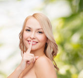 Beautiful young woman pointing finger to lips — Stockfoto