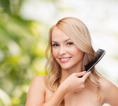 Smiling woman with hair brush — Photo