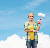Smiling woman in gloves with paint roller — Stock Photo