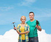 Smiling couple with hammer and drill — Stockfoto
