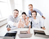 Group of office workers showing thumbs up — Stock Photo