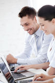 Man and woman working with laptop in office — Photo