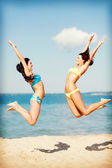Girls jumping on the beach — Photo