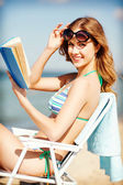 Girl reading book on the beach chair — Stock Photo
