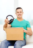 Opening cardboard box and taking out headphones — Stock Photo