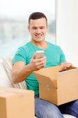 Opening cardboard box and taking out smartphone — Stock Photo