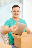 Opening cardboard box and taking out tablet pc — Stock Photo