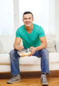 Smiling man watching sports at home — Stock Photo