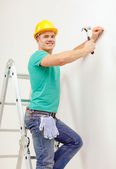 Smiling man in helmet hammering nail in wall — Stockfoto