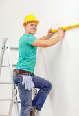 Smiling man building using spirit level to measure — Stock Photo