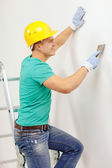Smiling man in helmet doing renovations at home — Stock Photo