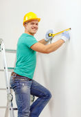 Smiling man in protective helmet measuring wall — Stock Photo