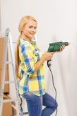 Woman with electric drill making hole in wall — ストック写真