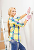 Smiling woman in gloves doing renovations at home — Stock Photo