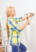 Smiling woman hammering nail in wall — ストック写真