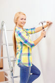 Smiling woman hammering nail in wall — Stock Photo