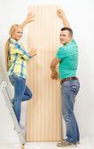 Sorrindo par escolher papel de parede para nova casa — Foto Stock