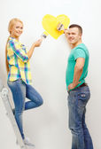 Smiling couple painting small heart on wall — Stockfoto