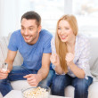 Smiling couple with popcorn cheering sports team — Stock Photo