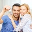 Smiling couple holding keys at home — Stock Photo
