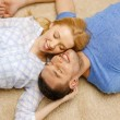 Smiling happy couple lying on floor at home — Stock Photo #43328577