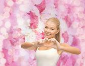 Smiling woman showing heart shape gesture — Stok fotoğraf