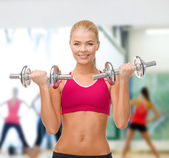 Smiling woman lifting steel dumbbells — Stockfoto
