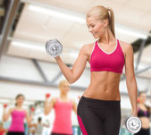 Smiling woman lifting steel dumbbell — Stock Photo
