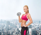 Smiling woman with heavy steel dumbbell — 图库照片