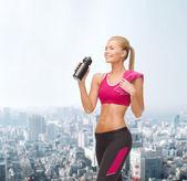 Sporty woman drinking water from sportsman bottle — Stock Photo