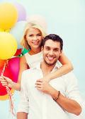 Casal com balões coloridos na beira-mar — Fotografia Stock