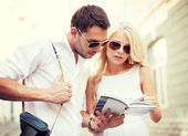 Couple with tourist book in the city — Stockfoto