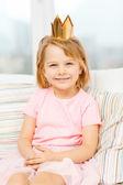 Smiling little girl in crown sitting on sofa — Stock Photo