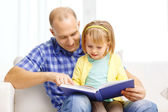 Smiling father and daughter with book at home — Stock Photo