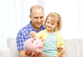 Happy father and daughter with big piggy bank — Stock Photo