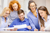 Smiling team with paper at office — Stock Photo