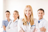 Female doctor or nurse in front of medical group — Stockfoto