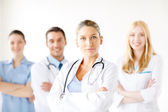 Serious female doctor in front of medical group — Stock Photo