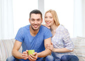 Smiling man with cup of tea or coffee with wife — Stockfoto