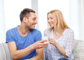 Smiling man giving cup of tea or coffee to wife — Stock Photo